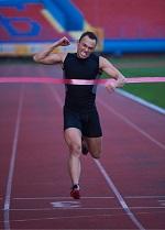 man running through finish line